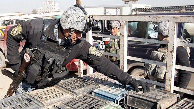 An Iraqi policeman at a checkpoint in Baghdad checks crates as attacks continue in and around the city. Photo: AFP