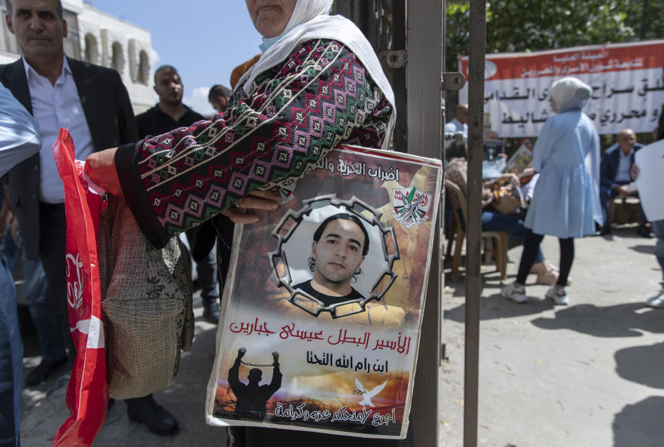 """A woman holds a poster with a picture of a Palestinian prisoner that reads """"the prisoner hero Issa Jabbareen, I starve for your dignity and pride"""" during a protest supporting prisoners, in the West Bank city of Ramallah, Tuesday, Sept. 14, 2021. Hundreds of thousands of Palestinians have passed through a military justice system designed for a temporary occupation that is now well into its sixth decade. Nearly every Palestinian has a loved one who has been locked up in that system at some point, and imprisonment is widely seen as one of the most painful aspects of life under Israeli rule. (AP Photo/Nasser Nasser)"""