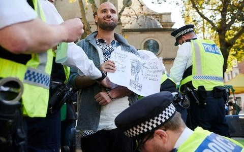 Police arrest a protester after issuing a section 14 notice at an Extinction Rebellion gathering - Credit: Thomas Bowles