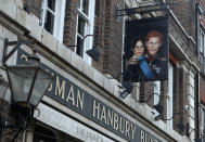 A sign showing Britain's Prince Harry and his wife Meghan, hangs outside the Duke of Sussex pub near Waterloo station, London, Tuesday March 9, 2021. Prince Harry and Meghan's explosive TV interview has divided people around the world, rocking an institution that is struggling to modernize with claims of racism and callousness toward a woman struggling with suicidal thoughts. (AP Photo/Tony Hicks)