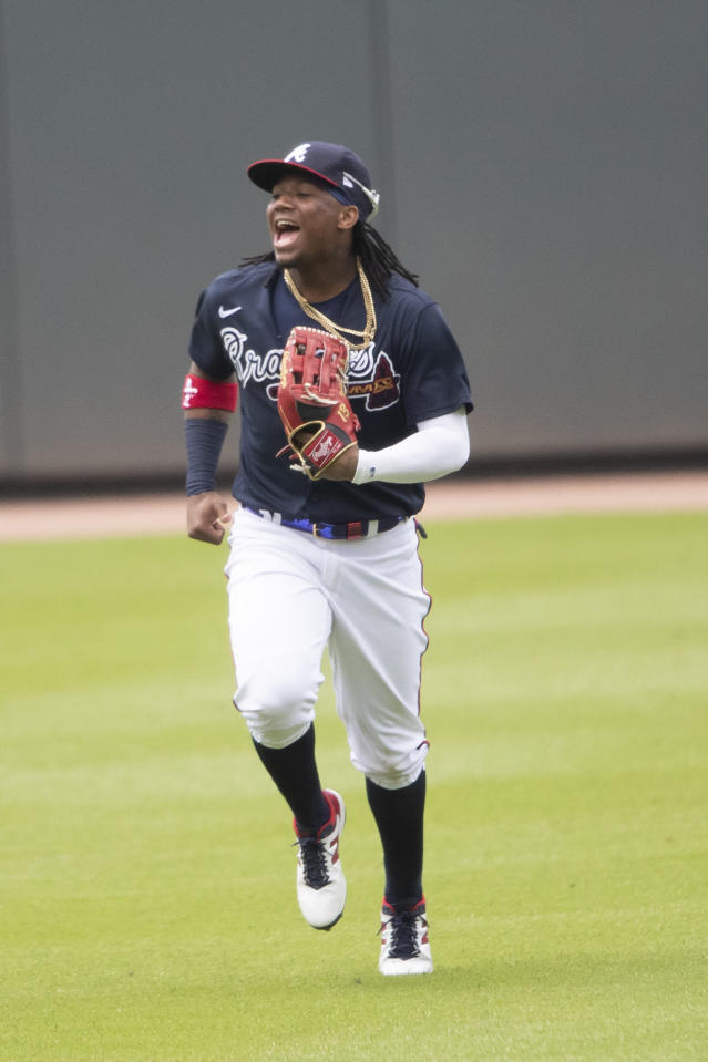 Atlanta Braves center fielder Ronald Acuna Jr. (13) jokes with teammates as he runs in from the outfield during a practice baseball game, Thursday, July 9, 2020, in Atlanta. (AP Photo/John Bazemore)