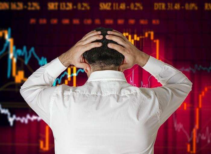 A man standing with his hands wrapped around the back of his head while watching a burgundy stock chart.