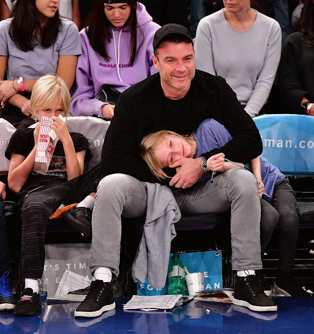 <p>The <em>Ray Donovan</em> star took his boys to see the New York Knicks play the Orlando Magic at Madison Square Garden Sunday night. While Alexander, 10, munched on popcorn, it seems Samuel, 8, got a little sleepy during the game — good thing he found the perfect place to lay his head for a quick time-out! (Photo: James Devaney/Getty Images) </p>