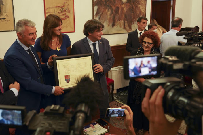 Catalan separatist leader Carles Puigdemont, right, flanked by Speaker of the Catalan Parliament Laura Borras exchanges gifts with Mayor of Alghero Mario Conoci, left, in Alghero, Sardinia, Italy, Saturday, Sept. 25, 2021. Puigdemont was visiting the city hall after he took a leisurely walk in the Sardinian city, waving to supporters, a day after a judge freed him from jail pending a hearing on his extradition to Spain, where the political firebrand is wanted for sedition. (AP Photo/Andrea Rosa)