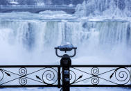 <p>A pair of binoculars looks over ice forming at the base of the American Fall as water flows over the falls as viewed from the Canadian side in Niagara Falls, Ont., Tuesday, Jan. 2, 2018. Almost every year frigid temperatures transform the falls into an icy winter wonderland when the mist is blown back, freezing on the landscape. (Aaron Lynett/The Canadian Press via AP) </p>