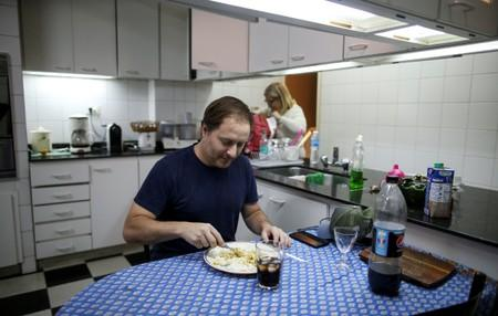 Guillermo Galia eats lunch at his home, in Buenos Aires