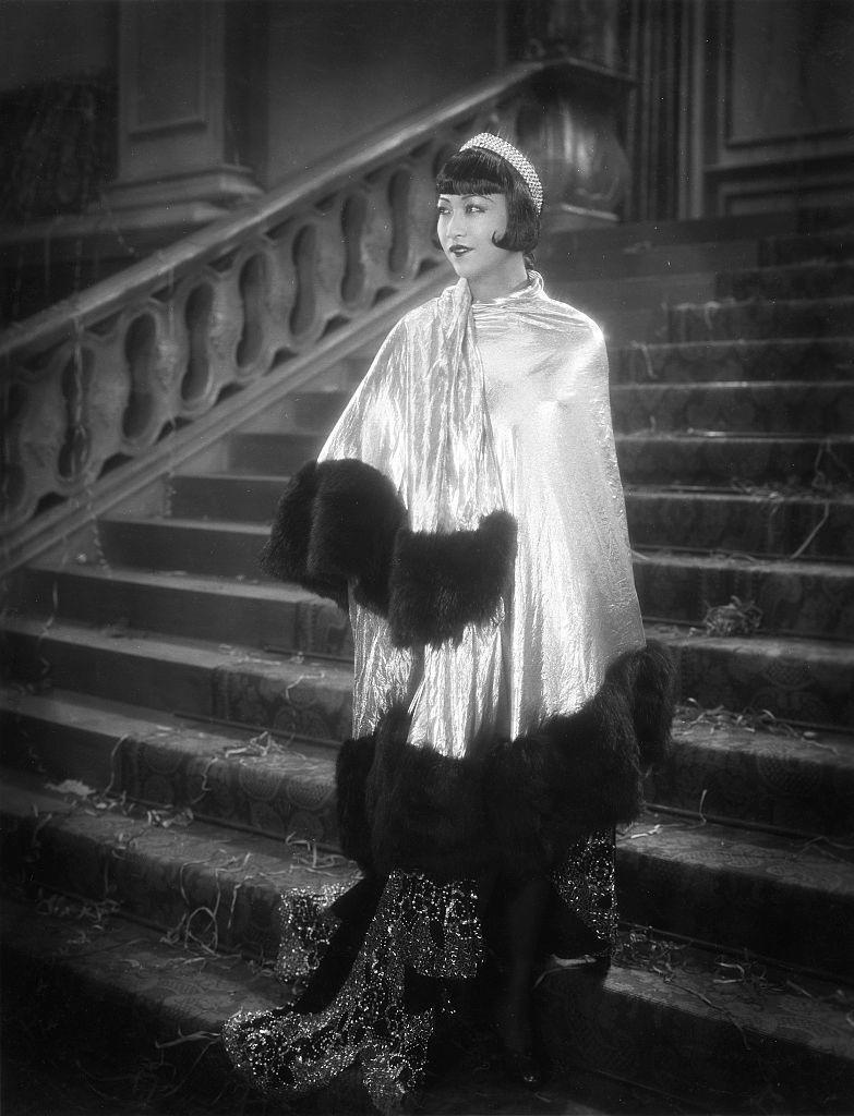 """<p>Anna May Wong's glittering diamond headpiece completes her opulent wardrobe in the British-German film, <em>Pavement Butterfly</em>. While the diadem is iconic because of its sparkling jewels, the actress wearing it made an even larger impact on the industry as one of the <a href=""""https://www.veranda.com/luxury-lifestyle/luxury-fashion-jewelry/g36433938/anna-may-wong-style/?slide=4"""" rel=""""nofollow noopener"""" target=""""_blank"""" data-ylk=""""slk:very first"""" class=""""link rapid-noclick-resp"""">very first</a> Chinese-American stars to be cast as a romantic lead.</p>"""