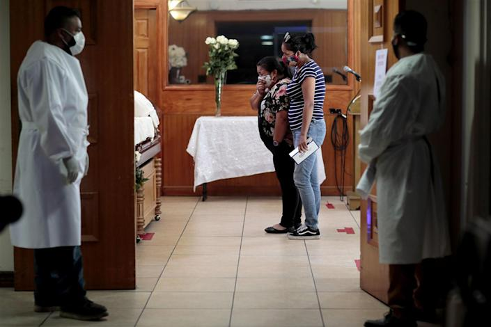 Iris Martinez weeps as she stands 3 feet from her father's casket while her best friend comforts her in Los Angeles on Aug. 5.