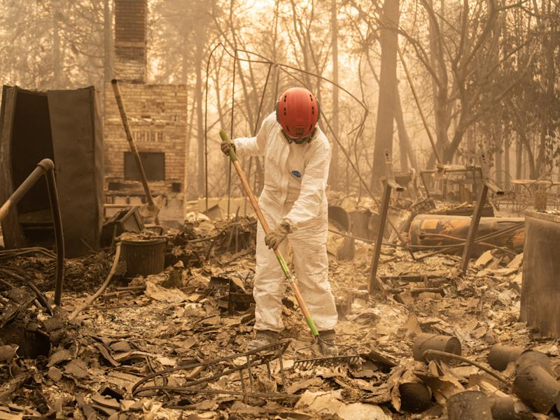 A member of the Tuolumne County Sheriff's Search & Rescue Team looks for human remains at a burned home in Paradise.