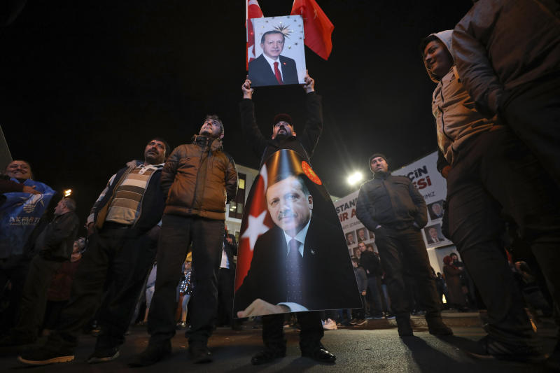 Supporters of President Recep Tayyip Erdogan holds his picture after the local elections, in Istanbul, Sunday, March 31, 2019. Erdogan's ruling party is leading in Sunday's municipal elections that he has depicted as a fight for Turkey's survival, but may lose control of the capital in the vote that is seen as a test of his support amid a sharp economic downturn. (AP Photo/Emrah Gurel)