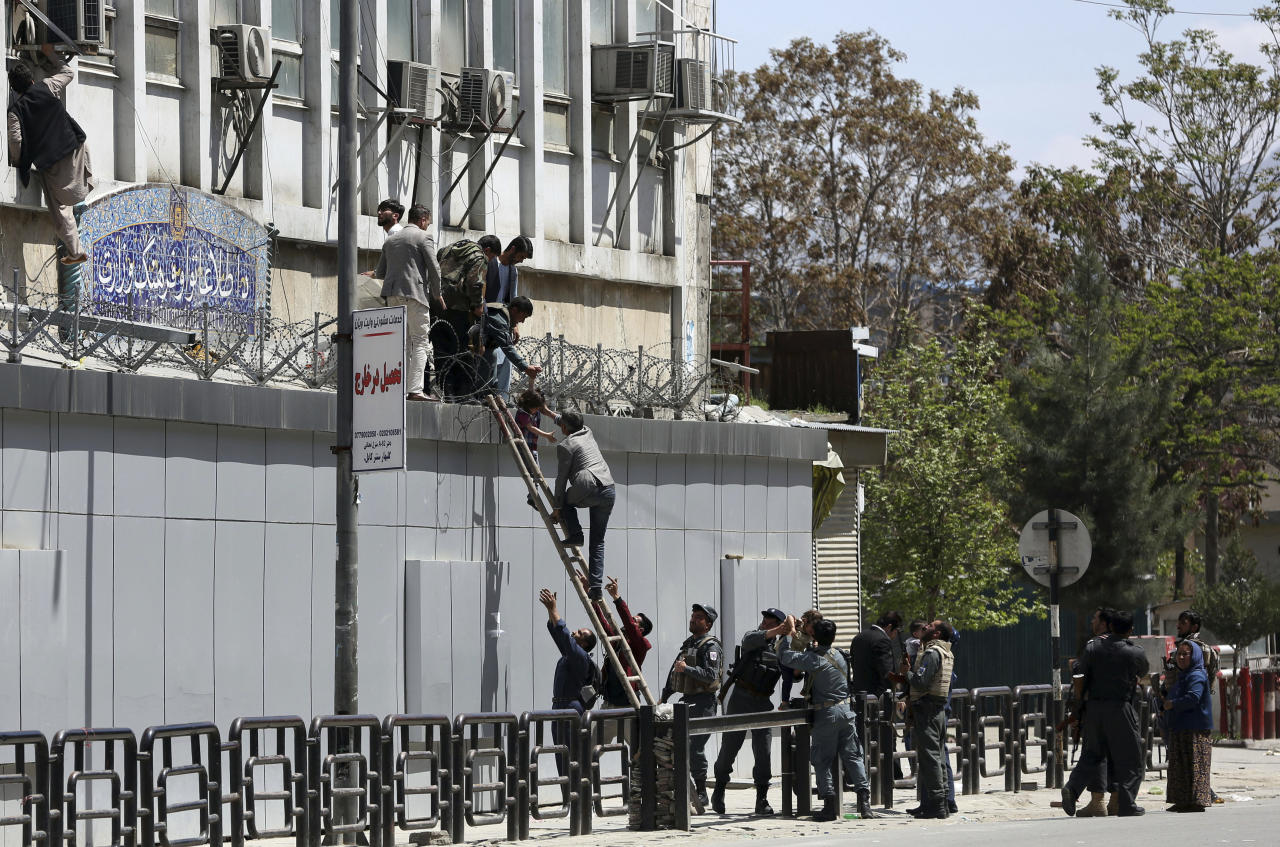 Afghan security personnel rescue men and children from the information and culture ministry after an attack near to the Telecommunication Ministry in Kabul, Afghanistan, Saturday, April 20, 2019. Afghan officials say an explosion has rocked the telecommunications ministry in the capital city of Kabul. Nasart Rahimi, a spokesman for the interior ministry, said Saturday the blast occurred during a shootout with security forces. (AP Photo/Rahmat Gul)
