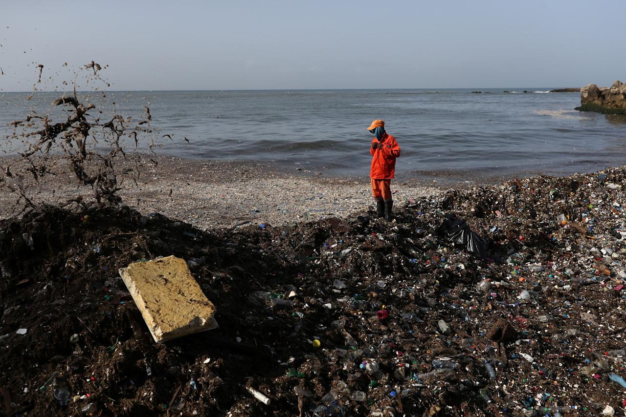 A worker from the Ministry of Public Works and Communications (MOPC) buttons his jacket before removing plastic and other debris during a cleanup on the shores of Montesinos beach, in Santo Domingo, Dominican Republic July 19, 2018. REUTERS/Ricardo Rojas