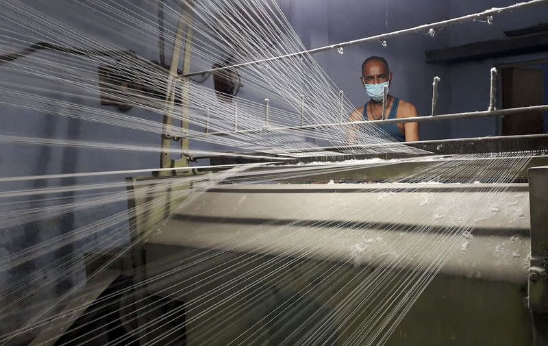 FILE PHOTO: A worker wearing a protective face mask works on a loom in a textile factory in Meerut
