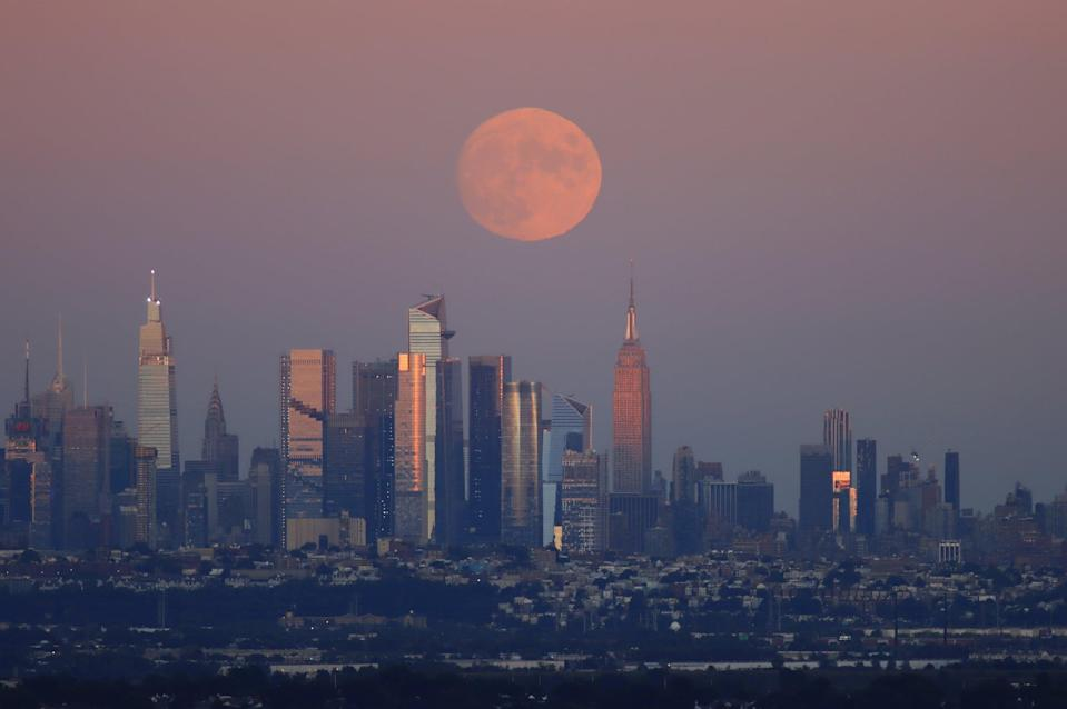 WEST ORANGE, NJ - SEPTEMBER 19: A 98.8 percent Harvest Moon rises behind midtown Manhattan, One Vanderbilt, the Chrysler Building, the Spiral, Hudson Yards and the Empire State Building as the sun sets in New York City on September 19, 2021 as seen from West Orange, New Jersey.  (Photo by Gary Hershorn/Getty Images)