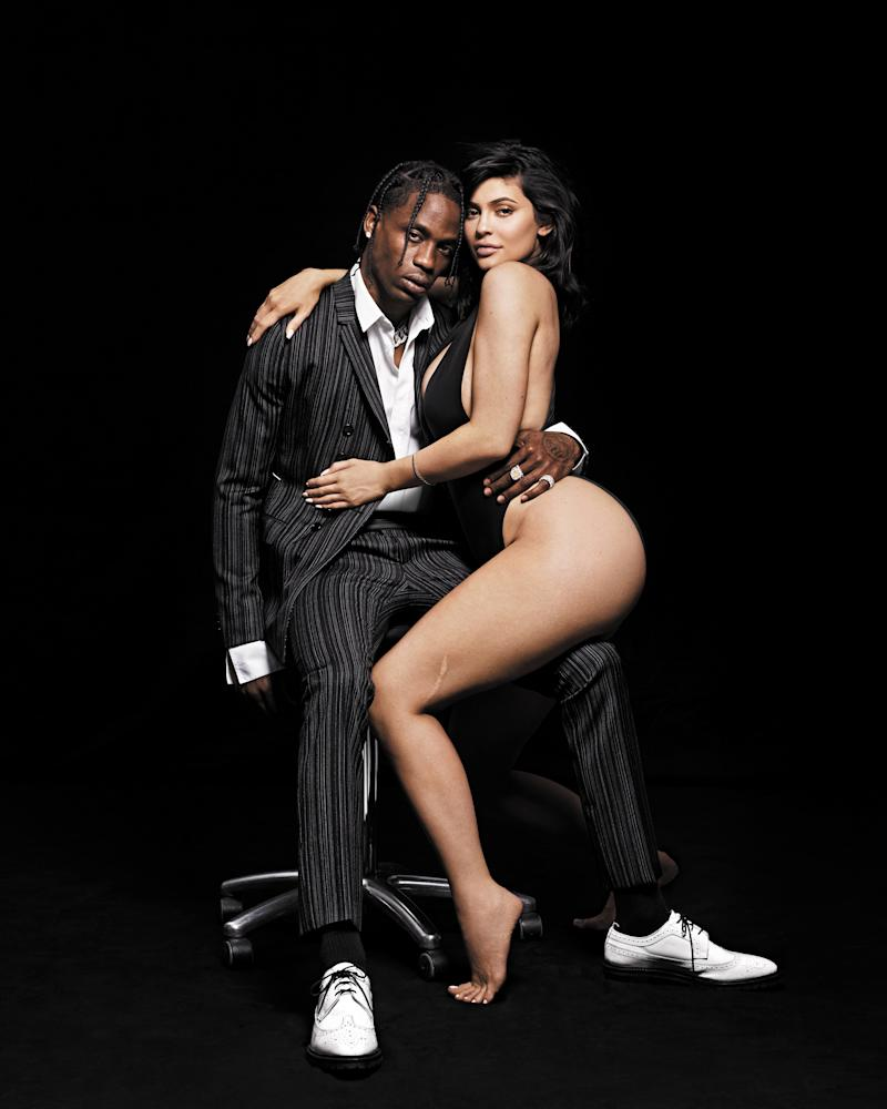 On Travis Scott and Kylie Jenner Blazer, $2,150, pants (price upon request), and shirt, $590, by Dior Homme. Shoes, $1,050, by Thom Browne. Socks, $19 (for three pairs), by Gold Toe. Jewelry, his own. Bodysuit by Norma Kamali. Bracelet, her own. Styled Throughout by Madeline Weeks.