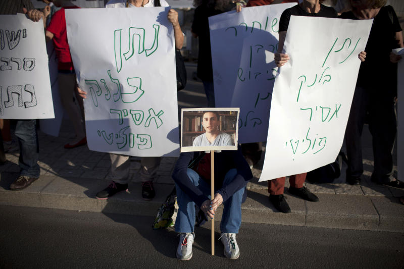 "Left wing activists hold signs during a protest calling for the release of Israeli conscientious objector Natan Blanc from military prison, in front of the ministry of defense office in Tel Aviv, Tuesday, May 21, 2013. The Israeli military has jailed Blanc for six months because of his opposition to Israel's occupation of the West Bank, in one of the most protracted cases by a conscientious objector in years. The refusal by 20-year-old Natan Blanc to serve in the military has shined a light on Israeli policies toward the Palestinians. It has also put the military in a delicate position as it tries to resolve the case, since releasing him could set an unwanted precedent while keeping him jailed could turn into a public relations debacle. Hebrew on signs read: ""Natan Blanc political prisoner."" (AP Photo/Oded Balilty)"