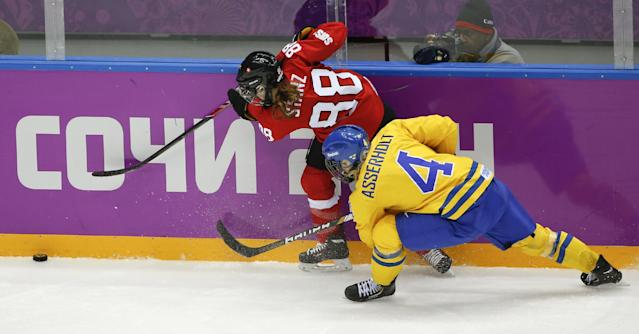 Phoebe Stanz of Switzerland (88) and Jenni Asserholt of Sweden (4) chase a loose puck during the second period of the women's bronze medal ice hockey game at the 2014 Winter Olympics, Thursday, Feb. 20, 2014, in Sochi, Russia. (AP Photo/Julio Cortez)
