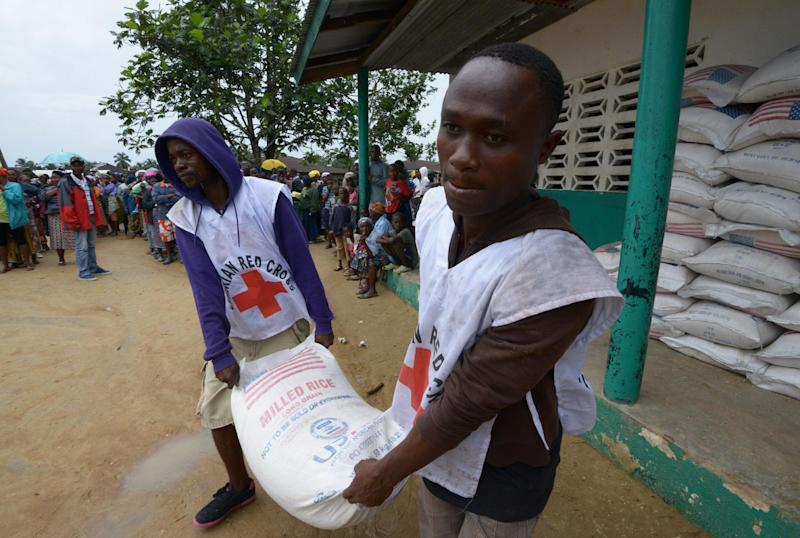 Members of the Liberian Red Cross carry a bag of rice during a food distribution by the World Food Programme in Dolo Town (AFP Photo/Dominique Faget)