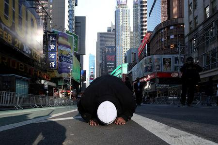 "FILE PHOTO: A Muslim man kneels on Broadway Ave. as he takes part in afternoon prayers during an ""I am Muslim Too"" rally in Times Square, Manhattan, New York, U.S. February 19, 2017.   REUTERS/Carlo Allegri/File Photo"