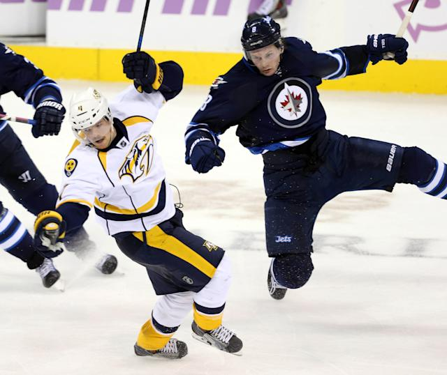 Nov 4, 2014; Winnipeg, Manitoba, CAN; Winnipeg Jets defenceman Jacob Trouba (8) hits Nashville Predators defenceman Ryan Ellis (4) during the third period at MTS Centre. Winnipeg wins 3-1. (Bruce Fedyck-USA TODAY Sports)