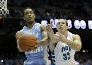 North Carolina's J.P. Tokoto, left, and UNC Wilmington's Shane Reybold (33) reach for the ball during the first half of an NCAA college basketball game in Chapel Hill, N.C., Tuesday, Dec. 31, 2013. (AP Photo/Gerry Broome)
