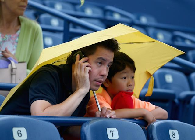 TORONTO, ON - AUGUST 07: Fans take cover as the rain falls during the Na Li of China match against Anastasia Pavlyuchenkova of Russia on day three of the Rogers Cup Toronto at Rexall Centre at York University on August 7, 2013 in Toronto, Ontario, Canada. (Photo by Andy Lyons/Getty Images)