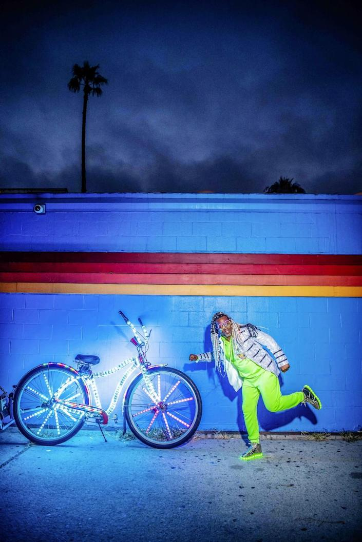 Marcus Gladney and his bike in front of a multicolored wall.