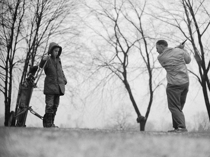 Low-angle view of American businessman and politician George W. Romney (1907 - 1995) and his son, future businessman and politician Mitt Romney, as they play golf, Bloomfield Hills, Michigan 1958.