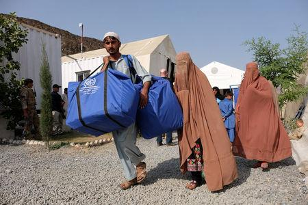 An Afghan family, who were living as refugees in Pakistan, carries bundles of supplies at a humanitarian aid station in Torkham, Afghanistan, October 22, 2016. REUTERS/Josh Smith