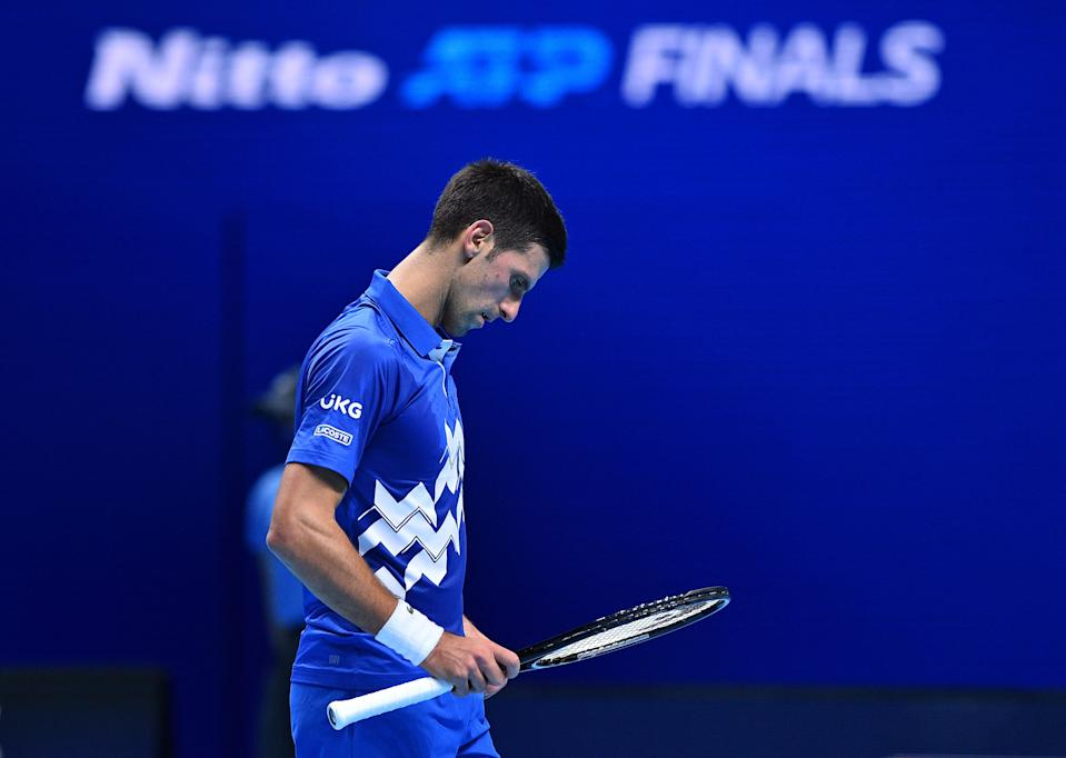 Novak Djokovic looks at his racquet in between points during the match against Daniil Medvedev.