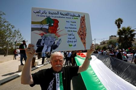 Palestinian demonstrator holds anti-Trump sign during a rally marking the 71st anniversary of the 'Nakba' in Ramallah in the Israeli-occupied West Bank