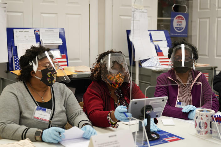 Election workers prepare to register voters on Election Day at a polling place inside the Bartow Community Center, Tuesday, Nov. 3, 2020, in the Bronx borough of New York. (AP Photo/Mark Lennihan)