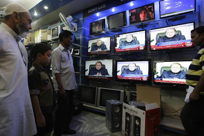 People watch Prime Minister of Pakistan Nawaz Sharif addressing the nation, at an electronic shop in Karachi, Pakistan, Monday, Aug. 19, 2013. Sharif has reiterated his offer to talk with militants who have so far rejected the prospect of negotiations. But he also held open the possibility of new military operations against militants who have waged a campaign of bombings and shootings that have killed thousands of civilians and security personnel. (AP Photo/Fareed Khan)