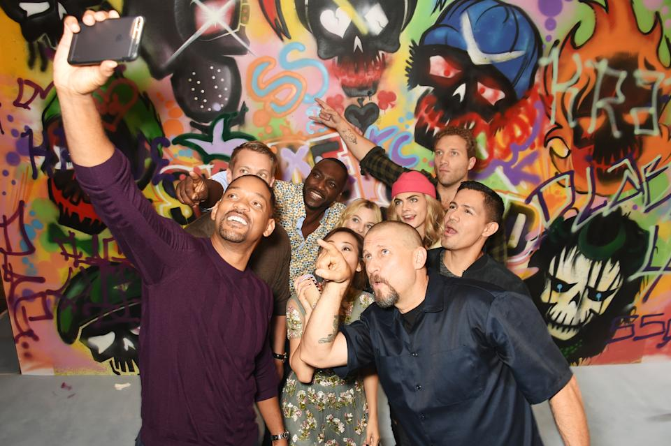 "LONDON, ENGLAND - AUGUST 04:  The cast of ""Suicide Squad"" including Will Smith, Joel Kinnaman, Adewale Akinnuoye-Agbaje, Karen Fukuhara, Margot Robbie, Cara Delevingne, Jai Courtney, Jay Hernandez and director David Ayer put the finishing touches on Graffiti artist Ryan Meades' mural ahead of tomorrow's film release on August 4, 2016 in London, United Kingdom.  (Photo by David M. Benett/Dave Benett/Getty Images for Warner Bros.)"