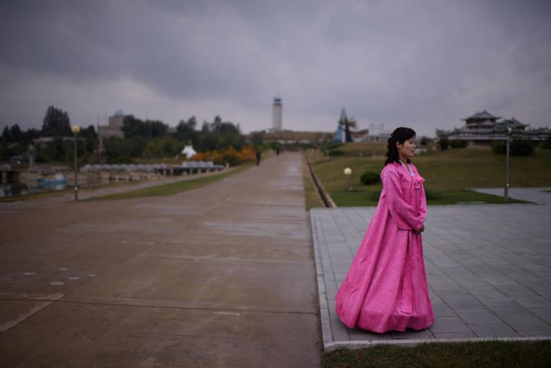 A North Korean tour guide wearing a traditional 'hanbok' dress waits for visitors at a 'Folk Park' on the outskirts of Pyongyang on October 11, 2015 (AFP Photo/Ed Jones)