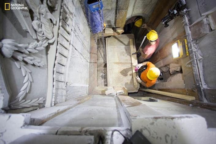 """Workers remove a marble slab covering the original stone """"burial bed"""" where Jesus Christ is said to have been laid to rest after being crucified. A layer of loose fill material is seen beneath. Scientists were surprised at how much of the original cave structure remained, said National Geographic archaeologist-in-residence Fredrik Hiebert. <cite>DUSAN VRANIC/NATIONAL GEOGRAPHIC</cite>"""