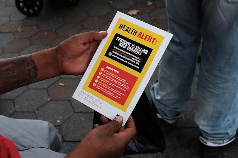 NEW YORK, NY - AUGUST 08: A heroin user reads an alert on fentanyl before being interviewed by John Jay College of Criminal Justice students as part of a project to interview Bronx drug users in order to compile data about overdoses on August 8, 2017 in New York City. The Bronx was the borough with the highest number of overdose deaths in 2016 with 308 residents. The students interview their subjects in a park and ask questions about their history of drug use and if they have overdosed.The subjects receive a small financial compensation for the research. (Photo by Spencer Platt/Getty Images)