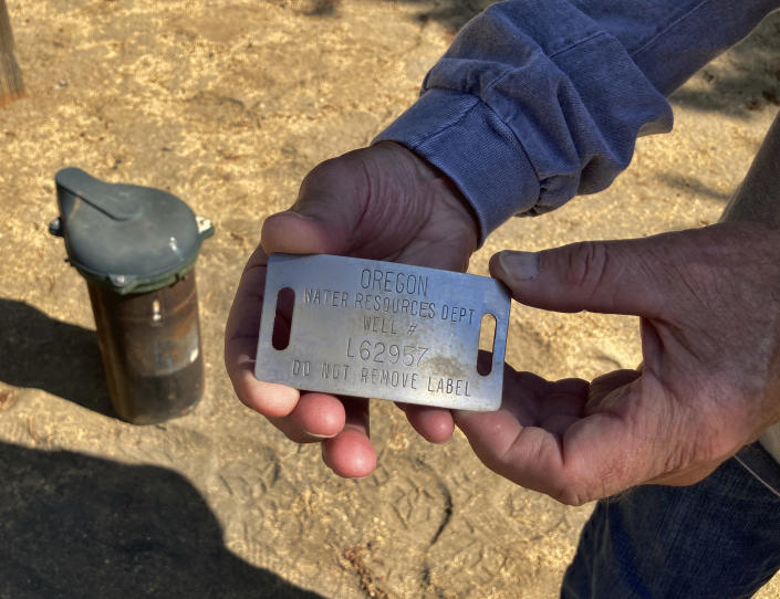 Jim Hooper holds the tag from his well in La Pine, Ore., on Aug. 26, 2021. The well number was checked against a database to determine when it was drilled and other details. Sheriff's deputies busted an illegal marijuana grow a block away recently and another, bigger grow had been nearby, using water from the same aquifer that the neighborhood uses. (AP Photo/Andrew Selsky)