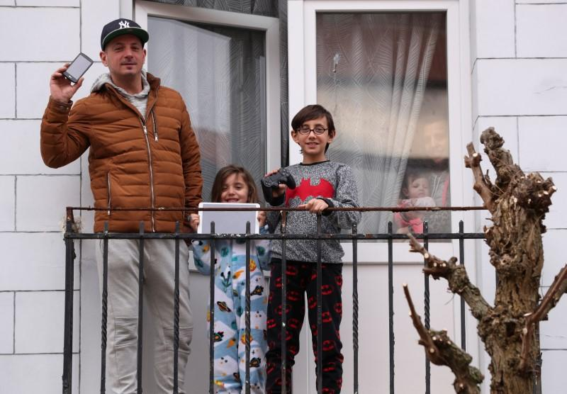 Resident Fernando and his children Enzo and Louna pose on the balcony of their home with objects significant to them during a coronavirus lockdown imposed by the Belgian government, in Brussels