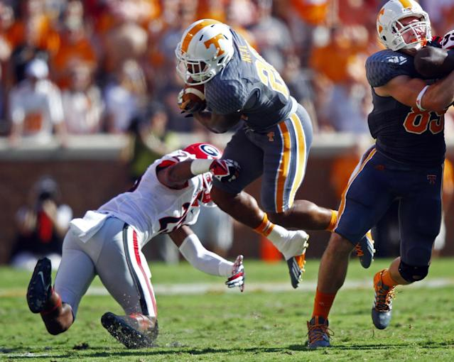 Tennessee's Rajion Neal (20) is tripped up by Georgia's Josh Harvey-Clemons (25) in the first half of an NCAA college football game on Saturday, Oct. 5, 2013, in Knoxville, Tenn. (AP Photo/Wade Payne)