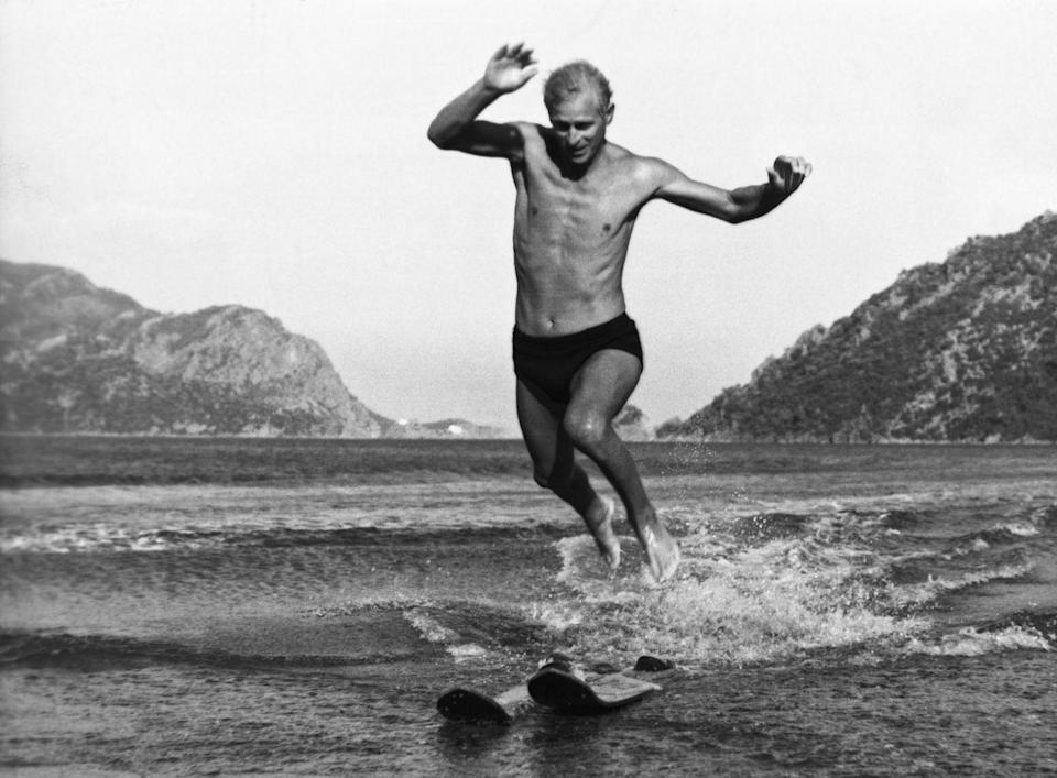 """<p>This shot of a young Prince Philip jumping off water skis was taken from a beach in Marmarice, Turkey. It was during the Mediterranean Fleet's <a href=""""https://www.goodhousekeeping.com/uk/lifestyle/a552669/why-you-need-a-summer-cruise-to-the-med-or-baltic/"""" rel=""""nofollow noopener"""" target=""""_blank"""" data-ylk=""""slk:summer cruise"""" class=""""link rapid-noclick-resp"""">summer cruise</a>, Prince Philip's last cruise in HMS Magpie before he returned to the United Kingdom in August 1951.<br></p>"""