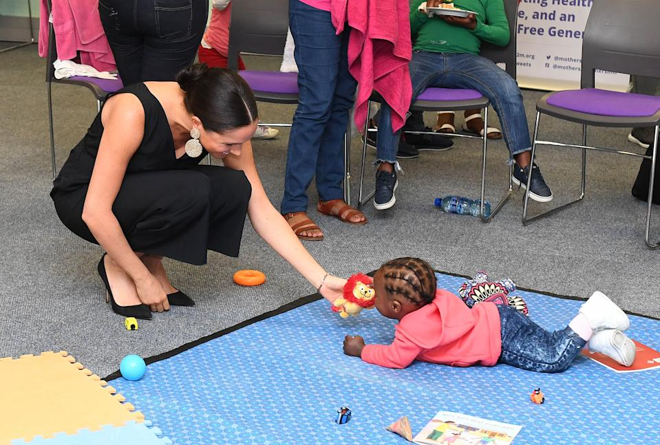 CAPE TOWN, SOUTH AFRICA - SEPTEMBER 25:  Meghan, Duchess of Sussex plays with 15 month old Asivile as she visits mothers2mothers during her royal tour of South Africa with Prince Harry, Duke of Sussex on September 25, 2019 in Cape Town, South Africa. mothers2mothers (m2m) is an African not-for-profit organisation with the vision of a healthy, HIV-free Africa. The organisation trains and employs women living with HIV as frontline health workers across eight African nations.  (Photo by Paul Edwards - Pool/Getty Images)