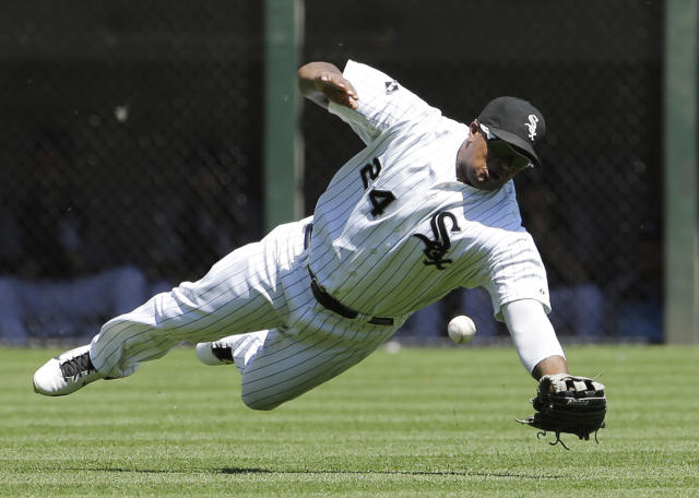 Chicago White Sox left fielder Dayan Viciedo can't make the catch on an RBI single hit by Kansas City Royals' Mike Moustakas during the fourth inning of a baseball game in Chicago on Saturday, June 14, 2014. (AP Photo/Nam Y. Huh)