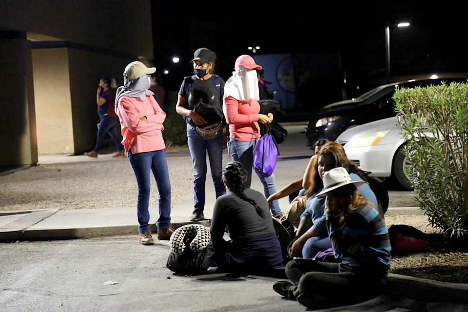 Migrant and seasonal day laborers gather outside a Chase parking lot to wait for buses that will take them to work on agricultural fields several miles away. (Christine Romo / NBC News)