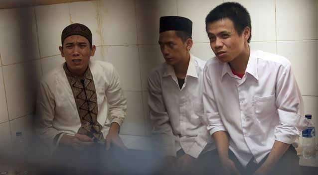 Child sexual abuse suspects, from left, Syahrial, Zainal Abidin and Virgiawan Amin sit inside a holding cell as they wait for the start of their trial at South Jakarta District Court in Jakarta, Indonesia, Wednesday, Aug. 27, 2014. Photo: Getty
