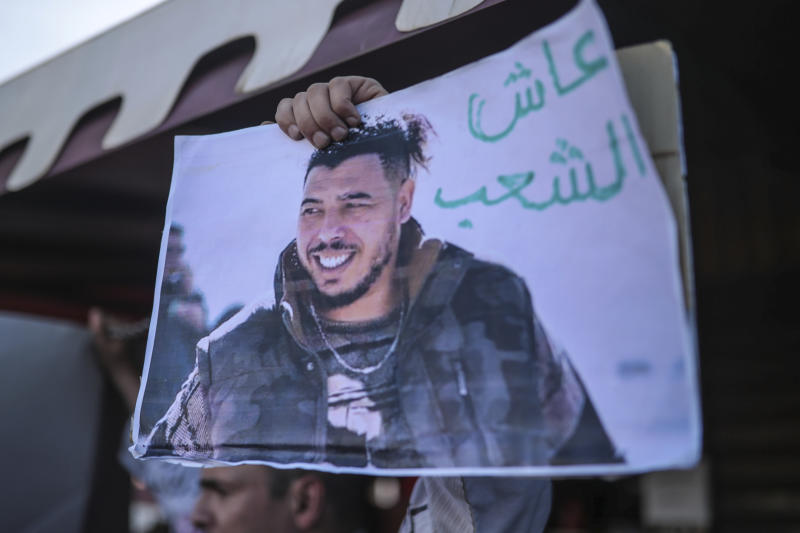 """FILE - In this Monday, Nov. 25, 2019, file photo, protesters carry a photo of Moroccan rapper Gnawi outside a court where he was on trial on charges of insulting the police, in Sale, Morocco. Banners in Arabic reads """"Long live the people."""" Referring to the title of the rap song which Gnawi released with 2 other rappers. Moroccan courts have sentenced a Youtuber who criticized the king to prison and also detained a journalist-activist who defended anti-government protesters in a tweet. (AP Photo/Mosa'ab Elshamy)"""