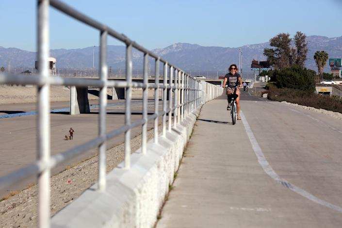 Bikers ride along a path along the Los Angeles River at its confluence with the Rio Hondo in South Gate.