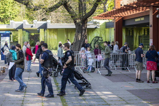 Police pass by as visitors line up to enter the Zoo on 28 April 2020 in Berlin, Germany. The aquarium, animal houses and playgrounds will remain closed for the time being.(Maja Hitij/Getty Images)