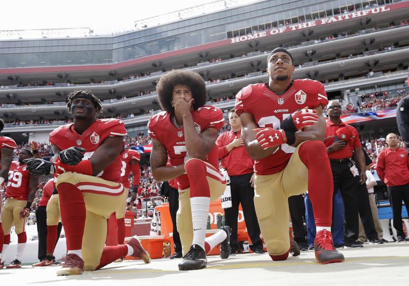 From left, San Francisco 49ers outside linebacker Eli Harold, quarterback Colin Kaepernick and safety Eric Reid kneel during the national anthem before an NFL game in 2016. (AP Photo/Marcio Jose Sanchez, File)