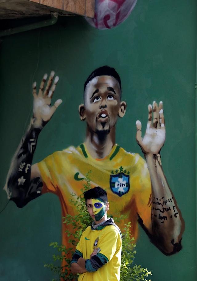A fan stands next to the painted image of Brazilian soccer player Gabriel Jesus in the neighbourhood where Gabriel Jesus lived in his childhood in Sao Paulo, Brazil June 17, 2018. REUTERS/Paulo Whitaker
